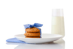 Stack of three homemade oatmeal cookies tied with blue ribbon in small white polka dots on white ceramic plate on matching blue na Stock Photos