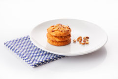 Stack of three homemade peanut butter cookies and peanuts on white ceramic plate on blue napkin Royalty Free Stock Photography