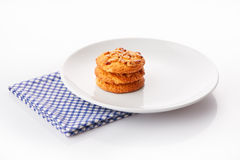 Stack of three homemade peanut butter cookies on white ceramic plate on blue napkin Royalty Free Stock Photography
