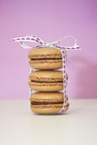 A stack of three macarons. A stack of three chocolate macarons Royalty Free Stock Image