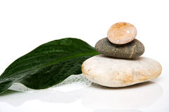 Stack of three rounded rocks. With green leaf on a white background royalty free stock photos