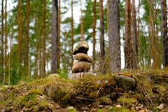 A stack of three stones in the forest among the trees stock photos