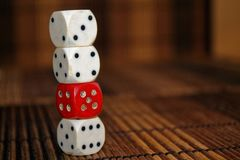 Stack of three white plastic dices and one red dice on brown wooden board background. Six sides cube with black dots. Number 3, 4,. 5, 6 stock images