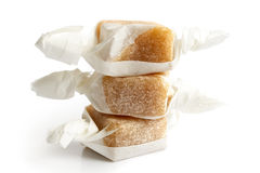 Stack of three wrapped vanilla caramel toffees . Stock Image