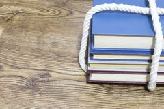 Stack of tied books on wooden background. royalty free stock image