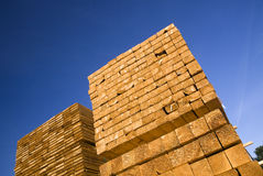 Stack of timber. Low angle with of tall stack of cut wood or timber with blue sky background Stock Photo