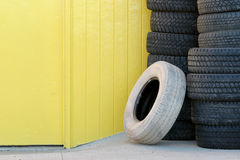Stack of tires against yellow wall. Stack of tires / tyres against yellow wall and door, one odd white tire leaning against the others Stock Photography