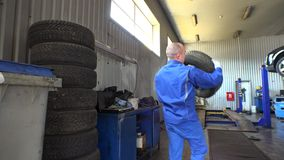 Stack of tires and male mechanic take one. Seasonal car tire changing in garage. Storing tires in repair shop stock footage