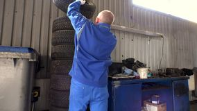 Stack of tires and mechanic take one. Seasonal car tire change in garage. Storing services stock video footage