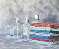 Stack of towels for bathroom bottles on a white marble background, space for text, selective focus Royalty Free Stock Photography