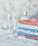 Stack of towels for bathroom bottles on a white marble background, space for text, selective focus Stock Photos