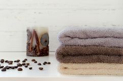 Stack of towels, candy, coffee beans on white wooden background stock photos