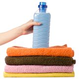 A stack of towels liquid powder conditioner softener in hand. On a white background isolation Stock Images