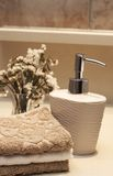Stack of towels and soap in the bathroom. Stack of white and brown towels and bottle of liquid soap with some dry flowers in the bathroom Stock Image