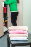 Stack of towels on table in foreground and housewife Royalty Free Stock Image