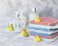 Stack of towels with yellow rubber bath ducks on white marble background, space for text, selective focus Stock Photos