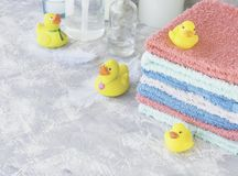 Stack of towels with yellow rubber bath ducks on white marble background, space for text, selective focus Royalty Free Stock Images
