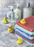 Stack of towels with yellow rubber bath ducks on white marble background, space for text, selective focus Royalty Free Stock Photo