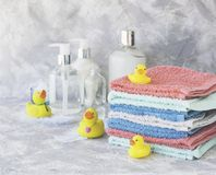 Stack of towels with yellow rubber bath ducks on white marble background, space for text, selective focus Stock Photography