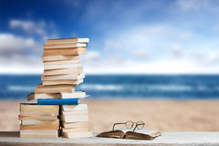 Stack of Travel Guides before a empty Beach Royalty Free Stock Photo