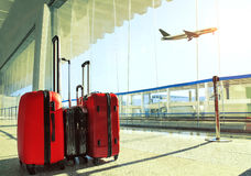Stack of traveling luggage in airport terminal and passenger pla. Ne flying over sky Stock Images