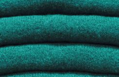 Stack of trend Quetzal Green woolen sweaters close-up, texture, background.  royalty free stock photo