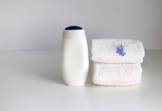 Stack of two white loop towels and bottles with cosmetic product. Royalty Free Stock Photography