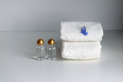 Stack of two white loop towels and bottles with cosmetic product. Royalty Free Stock Photos
