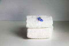 Stack of two white loop towels  - composition with little blue flowers Stock Photo