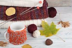 Stack ulltröjor Hög av den stack vintern, höstkläder på röd träbakgrund, tröjor, stickade plagg, boll, kopp Royaltyfri Fotografi