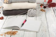 Stack ulltröjor Hög av den stack vintern, höstkläder på träbakgrund, tröjor, stickade plagg, penna, bok, utrymme Royaltyfri Bild
