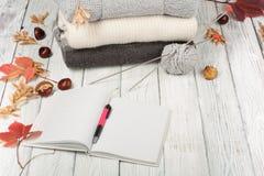 Stack ulltröjor Hög av den stack vintern, höstkläder på träbakgrund, tröjor, stickade plagg, penna, bok, utrymme Arkivbild