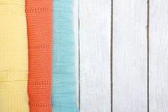 Stack ulltröjor Hög av stucken sommarkläder på träbakgrund, tröjor, stickade plagg, utrymme för text Arkivfoton