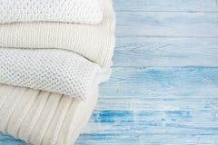 Stack ulltröjor Hög av stucken vinterkläder på blå träbakgrund, tröjor, stickade plagg, utrymme för text Fotografering för Bildbyråer
