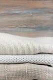 Stack ulltröjor Hög av stucken vinterkläder på träbakgrund, tröjor, stickade plagg, utrymme för text Royaltyfri Foto