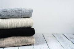 Stack ulltröjor Hög av stucken vinterkläder på träbakgrund, tröjor, stickade plagg, utrymme för text Royaltyfri Fotografi
