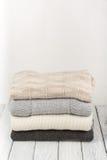 Stack ulltröjor Hög av stucken vinterkläder på träbakgrund, tröjor, stickade plagg, utrymme för text Royaltyfri Bild