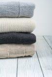 Stack ulltröjor Hög av stucken vinterkläder på träbakgrund, tröjor, stickade plagg, utrymme för text Royaltyfria Foton