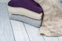 Stack ulltröjor Hög av stucken vinterkläder på träbakgrund, tröjor, stickade plagg, utrymme för text Arkivfoto