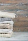 Stack ulltröjor Hög av stucken vinterkläder på träbakgrund, tröjor, stickade plagg, utrymme för text Arkivbilder