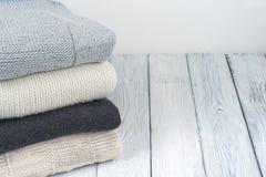 Stack ulltröjor Hög av stucken vinterkläder på träbakgrund, tröjor, stickade plagg, utrymme för text Arkivfoton