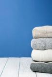 Stack ulltröjor Hög av vinterkläder på blå träbakgrund, stickade plagg, utrymme för text Arkivfoton