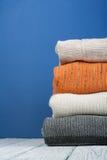 Stack ulltröjor Hög av vinterkläder på blå träbakgrund, stickade plagg, utrymme för text Royaltyfri Bild