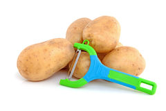 Stack of unpeeled potatoes and peeling knife Stock Images