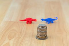 Stack of US coins, American money with blurred red blue dinosaur Stock Image