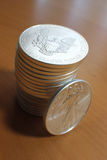 Stack of US Silver Eagle Coins. A stack of US Silver Eagles, with an out-of-focus background stock image