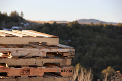 Stack of Used Pallets. A stack of used pallets with forest and mountains in the background Stock Image