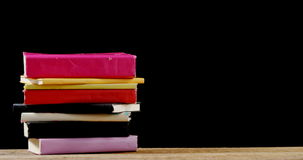 Stack of various book on table. Against black background stock video