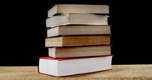 Stack of various book on table. Against black background stock footage