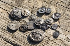 Some Greek metal ancient coins. Stack of various Greek ancient coins above wood background, Athens, Greece stock images